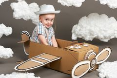 The boy plays in an airplane made of cardboard box and dreams of becoming a pilot, clouds from cotton wool on a gray background, r stock photo