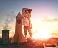 Boy plays astronaut. Little child boy plays astronaut. Child on the background of sunset sky. Child boy in an astronaut costume standing on the roof of the house royalty free stock photography