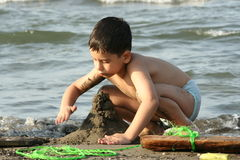 BOY PLAYS ON BEACH Stock Photography