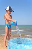 Boy plays on a beach stock image