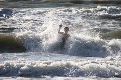 Boy plays big waves sea Royalty Free Stock Photo