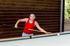 The boy plays billiards in the open air royalty free stock photography