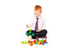 A boy  plays with blocks. On a white background Royalty Free Stock Image