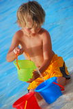 Boy plays with buckets by pool Stock Photography
