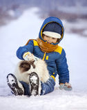Boy plays with cat outdoors in winter, child petting kitten sitt Stock Images