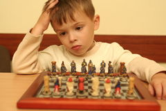 The boy plays a chess. Behind a table Stock Photo