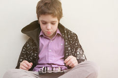 Boy plays with chess Royalty Free Stock Photography