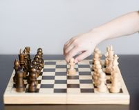 Boy plays chess and makes the first move a pawn Stock Images