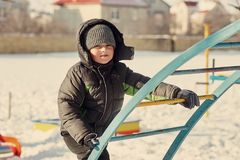 Boy on a cold day on the Playground. A boy plays on a cold day on the Playground Royalty Free Stock Photo