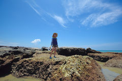 A boy plays exploring at the beach rocks. royalty free stock images