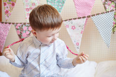 Boy plays at the festival with flags on background Royalty Free Stock Photo