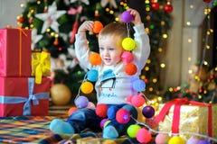 Boy plays a festive garland. Stock Photo