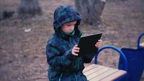 Boy plays a game on his tablet sitting in the Park on a bench. Boy plays a game on his tablet sitting in the Park on a bench stock video