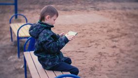 Boy plays a game on his tablet sitting in the Park on a bench. Side view. Boy plays a game on his tablet sitting in the Park on a bench stock footage