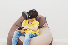 Boy plays game with virtual reality glasses indoors Royalty Free Stock Photos