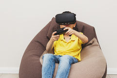 Boy plays game with virtual reality glasses indoors Stock Images