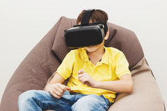 Boy plays game with virtual reality glasses indoors Stock Photo