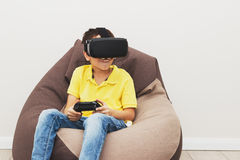 Boy plays game with virtual reality glasses indoors Royalty Free Stock Photo