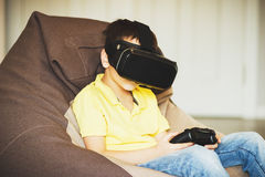 Boy plays game with virtual reality glasses indoors Stock Photography