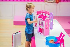 The boy plays with girl toys and dolls.  Stock Photo