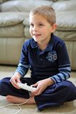 Boy plays handheld video game. A cute 6-year-old boy, with blond hair and perfect white teeth, holds the controllers for a Wii video game as he plays the game Stock Image