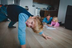 Boy plays at home while father is doing homework with daughter stock images
