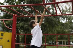 Boy  plays on horizontal bars. Boy teen plays on horizontal bars Royalty Free Stock Photo