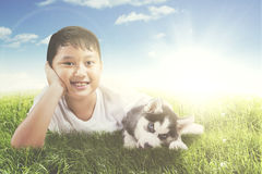Boy plays with husky puppy on the meadow Stock Photo