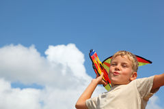 Boy plays kite against sky Stock Photo