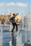Boy plays in London fountain. LONDON, UK - MARCH 25, 2016: Boy plays in the fountains on the Southbank of the Thames with Tower of London in background Stock Image