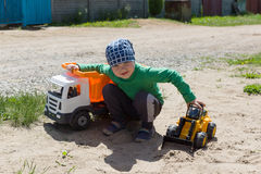 The boy plays with machines on the street Stock Images