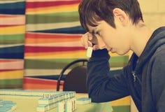 Boy plays Mahjong Stock Photography