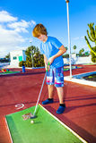 Boy plays minigolf Royalty Free Stock Photo