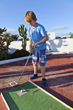 Boy plays minigolf Stock Photo