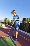 Boy plays minigolf Royalty Free Stock Images