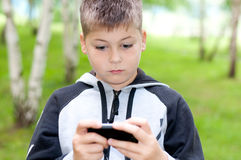 Boy plays on a mobile phone in a park Royalty Free Stock Photos