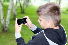 Boy plays on a mobile phone in a park Stock Photos