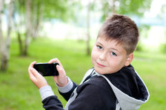 Boy plays on a mobile phone in a park Royalty Free Stock Photography