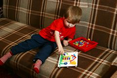 Boy plays with a mosaic Royalty Free Stock Images