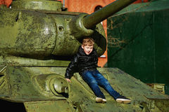 A boy plays in the Museum of military equipment Royalty Free Stock Images