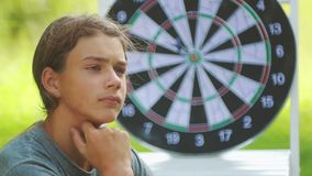 A boy plays an outdoor darts game. Portrait of a teenager boy playing darts. A boy plays an outdoor darts game stock video footage