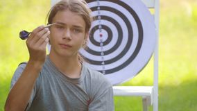 A boy plays an outdoor darts game. Portrait of a teenager boy playing darts. A boy plays an outdoor darts game stock video