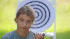 A boy plays an outdoor darts game. Portrait of a teenager boy playing darts. A boy plays an outdoor darts game stock footage