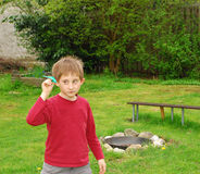 Boy plays with paper airplane in the garden. A boy stands with a paper airplane in a garden in the afternoon Royalty Free Stock Photo