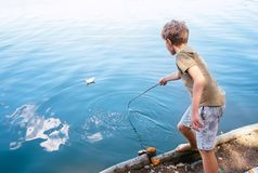 Boy plays with paper boat and launches it on the lake Royalty Free Stock Photography