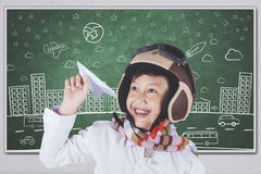 Boy plays a paper plane in class. Cheerful little boy playing a paper plane in the classroom while wearing helmet and scarf Royalty Free Stock Photography