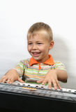 Boy plays piano. And smile Stock Image