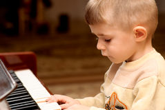 Boy plays piano Stock Image