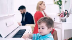 Boy plays the piano, his mother makes make-up in front of the mirror and his father reads a book in an expensive white. Interior, transfer focus. Rich parents stock video
