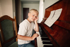 Boy plays piano at home. Little funny boy plays piano at home Royalty Free Stock Photo